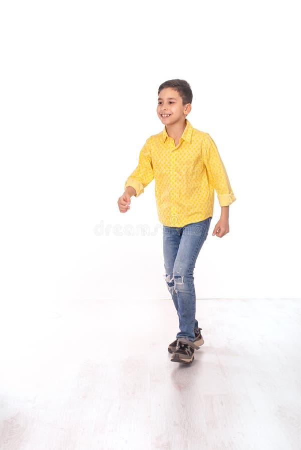 严肃的男孩的全长画象有胳膊横渡的佩带的黄色衬衣和牛仔裤的在白色背景在演播室 库存照片