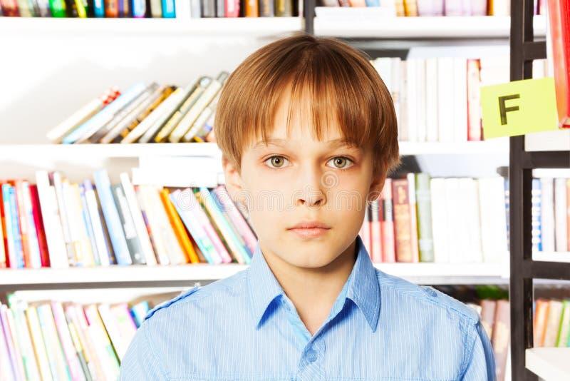 严肃的男孩画象在图书馆里 库存图片