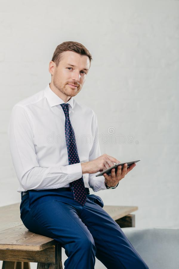 严肃的男性企业家观看在数字式片剂,与商务伙伴的消息的录影,优美地打扮,坐木tabl 库存照片