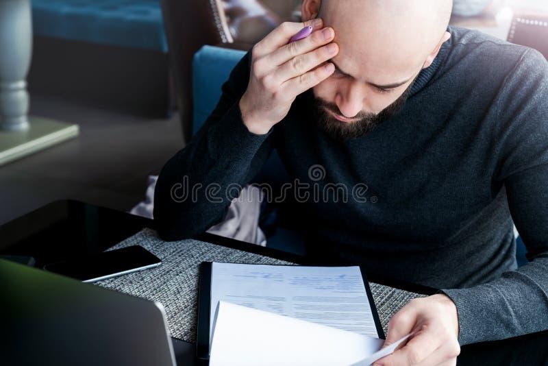 严肃的男性律师在咖啡馆坐在桌上并且在签字前读合同由客户 : ( 图库摄影