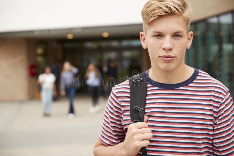 严肃的男性高中生画象在学院大厦之外的与其他少年学生在背景中 免版税库存图片