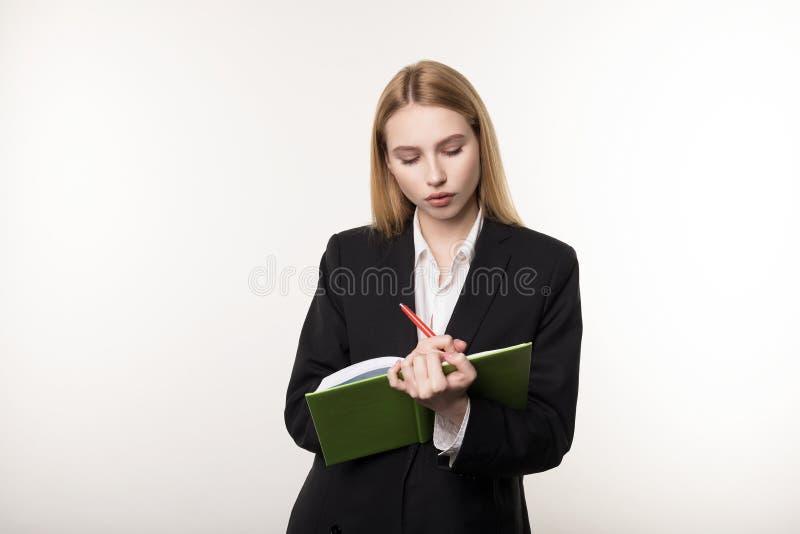 严肃的白肤金发的女实业家射击的腰部殷勤地听他的商务伙伴和作为的黑衣服的 库存照片