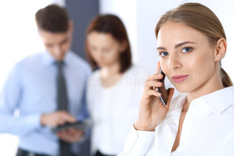 严肃的白肤金发的女实业家谈话由电话在她的同事背景中在办公室 到达天空的企业概念金黄回归键所有权 库存照片