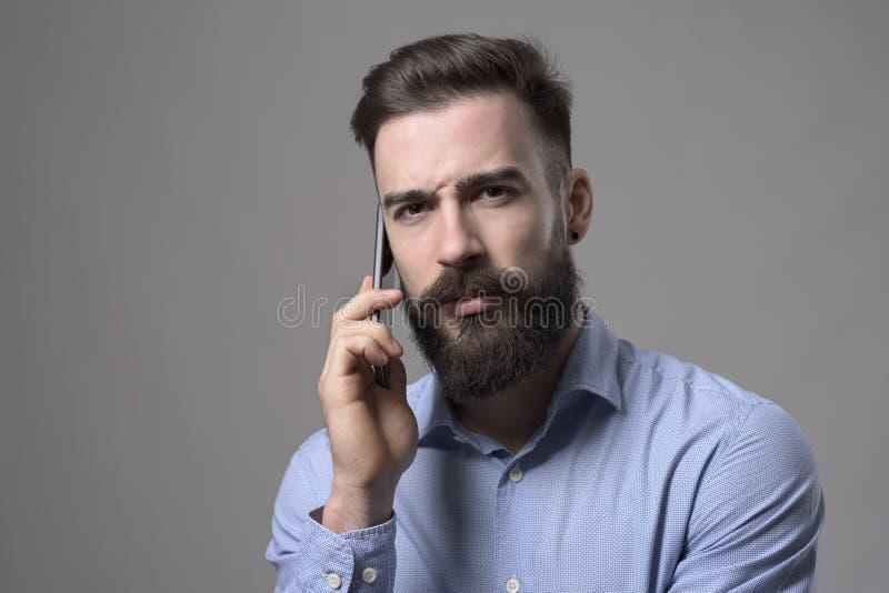 严肃的皱眉的年轻有胡子的商人谈话在有强烈的神色的手机在照相机 免版税库存照片