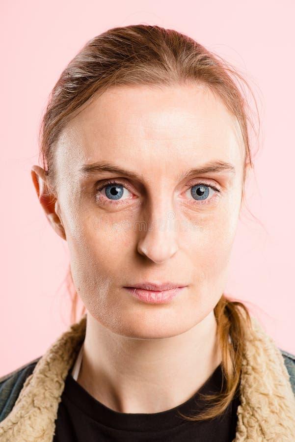 严肃的妇女画象桃红色背景真正的人民高definiti 库存照片