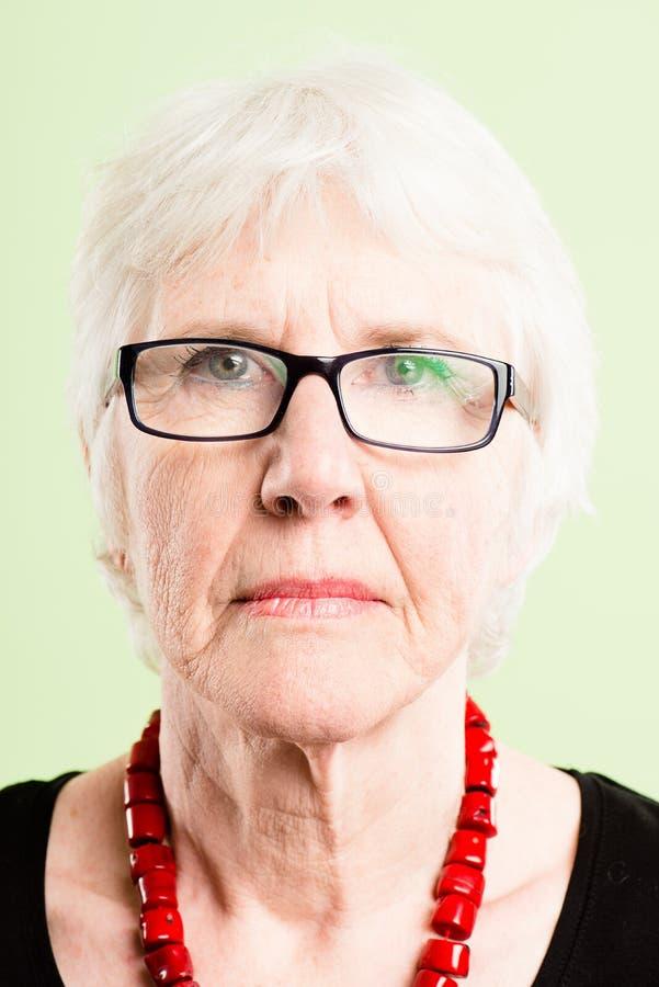 严肃的妇女画象真正的人民高定义绿色backgro 免版税图库摄影