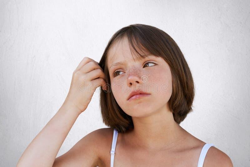 严肃的矮小的有雀斑的孩子,保留她的在头发的手, havin周道的表示,看在旁边 摆在反对的美丽的女孩 免版税库存照片