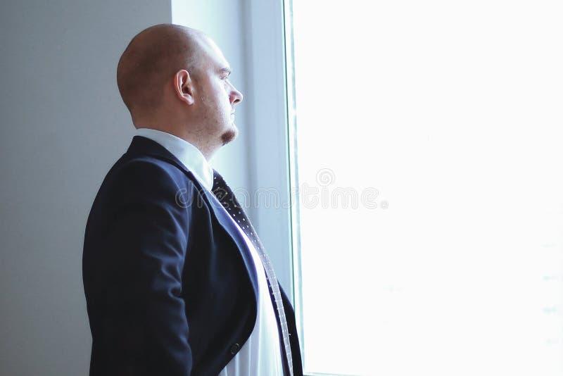 严肃的确信的商人看办公室的窗口 免版税库存照片