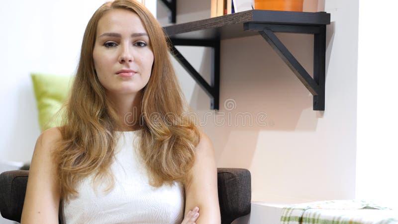 严肃的美丽的女孩画象,坐沙发 免版税库存图片