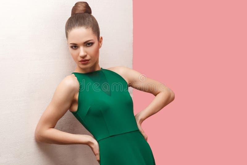 严肃的美丽的年轻女人画象有小圆面包发型和构成在绿色礼服身分用手在腰部和看的 库存图片