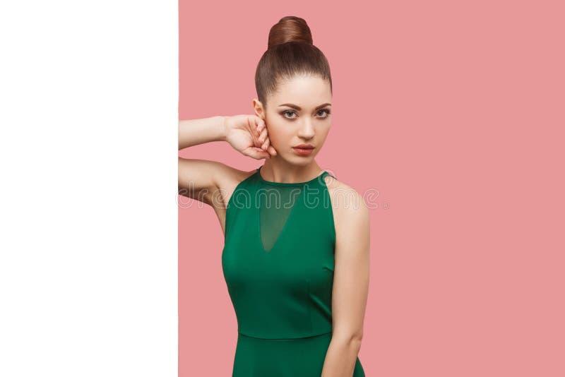 严肃的美丽的年轻女人画象有小圆面包发型的,在绿色礼服身分的构成在白色墙壁附近,接触她的面孔 库存照片