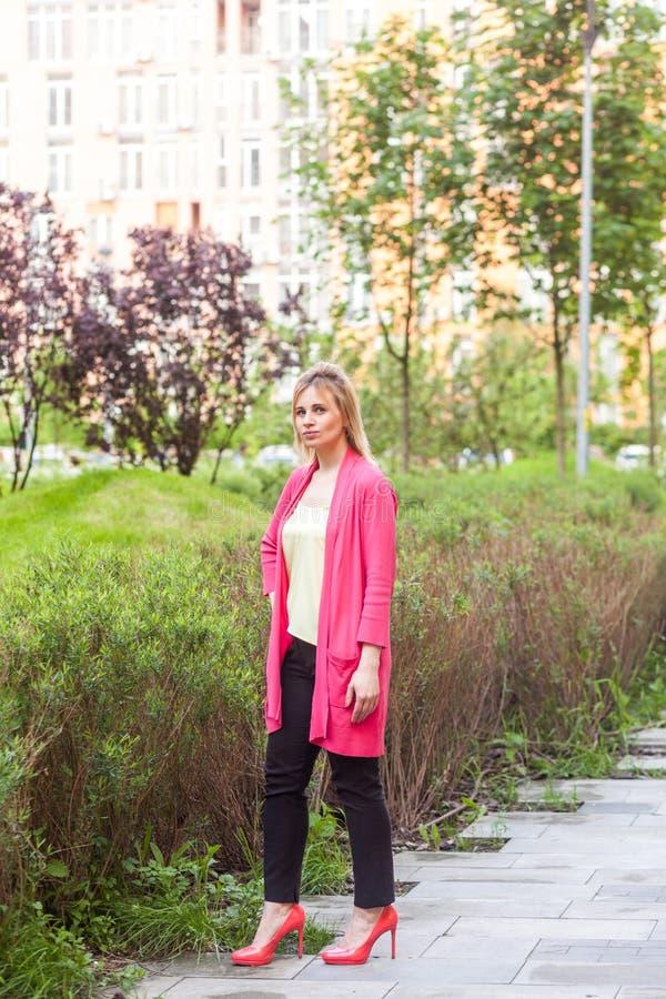 严肃的美丽的年轻成功的女实业家全长画象站立在绿色公园的高雅样式的,摆在与 免版税图库摄影