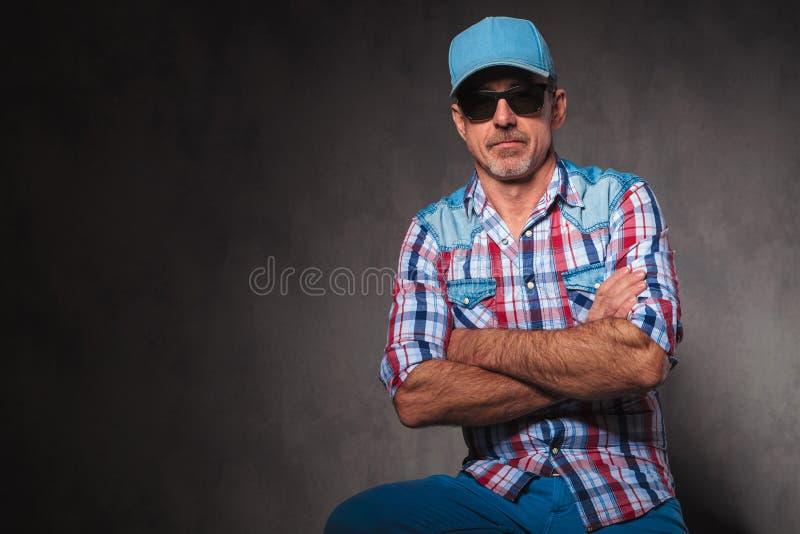 严肃的老偶然人佩带的太阳镜和棒球帽sitti 免版税库存图片