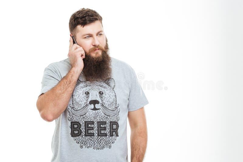 严肃的英俊的有胡子的人谈话在手机 免版税库存图片