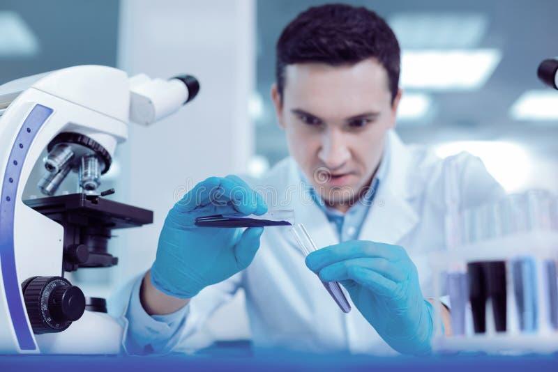 严肃的英俊的生物学家与新的疫苗一起使用 免版税库存照片