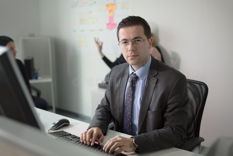 严肃的虔诚商人工作在计算机上的办公室 真正的经济学家商人,不是模型 银行雇员谈论 免版税图库摄影