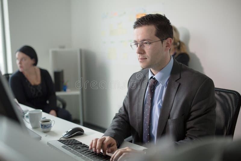 严肃的虔诚商人工作在计算机上的办公室 真正的经济学家商人,不是模型 银行雇员谈论 免版税库存照片