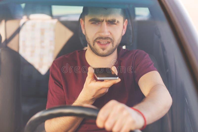 严肃的被集中的不剃须的深色的男性在交通ja驾驶汽车,做话音呼号,与同事讲话,为工作去,站立 免版税库存图片