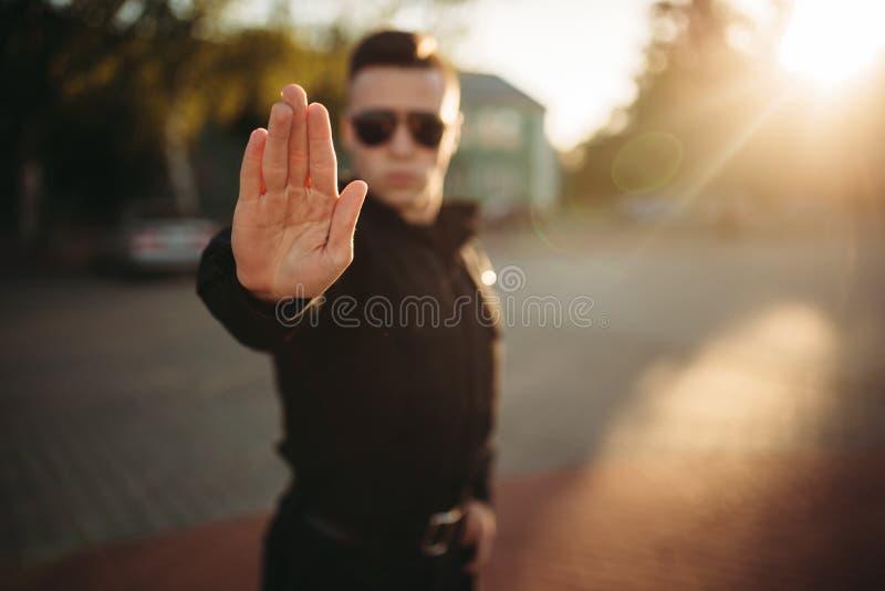 严肃的警察显示一个手停车牌 免版税库存照片