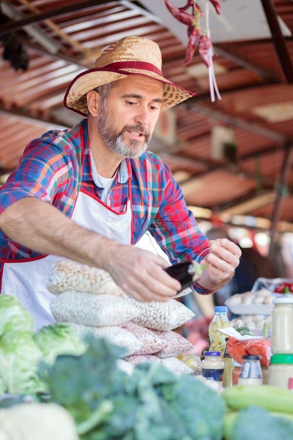 严肃的资深农场主销售有机蔬菜在一个地方市场 免版税库存照片