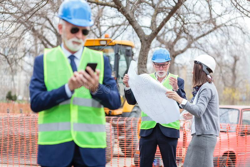 严肃的资深男性和看大厦图纸的年轻女性建筑师或者商务伙伴 库存图片