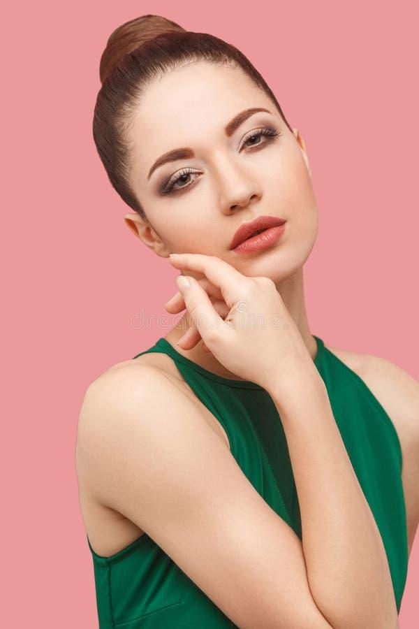 严肃的镇静美丽的年轻女人特写镜头画象有小圆面包发型和构成的在接触她的面孔的绿色礼服身分和 库存图片