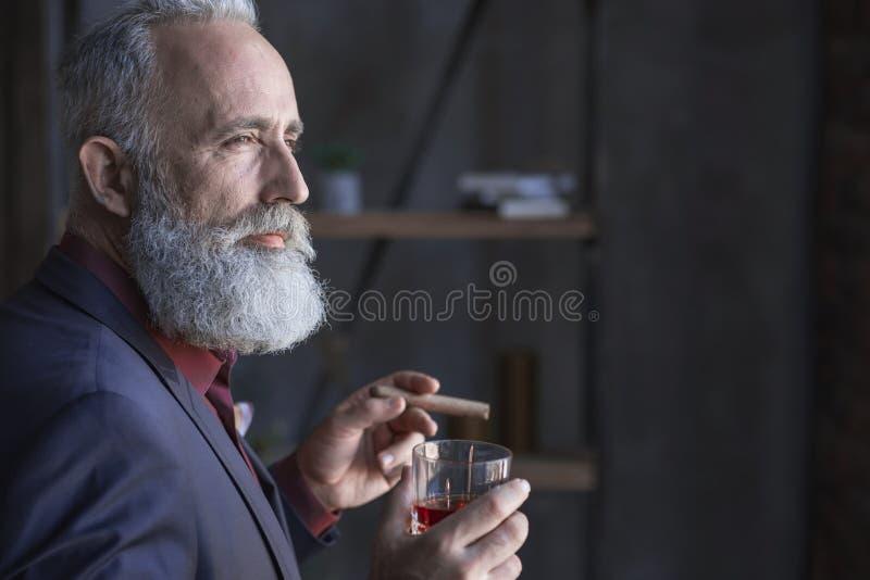 严肃的领抚恤金者品尝酒精和保持烟草 免版税库存图片