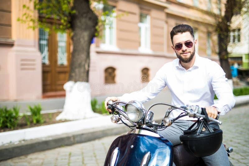 严肃的年轻商人画象在摩托车的在城市街道上 图库摄影