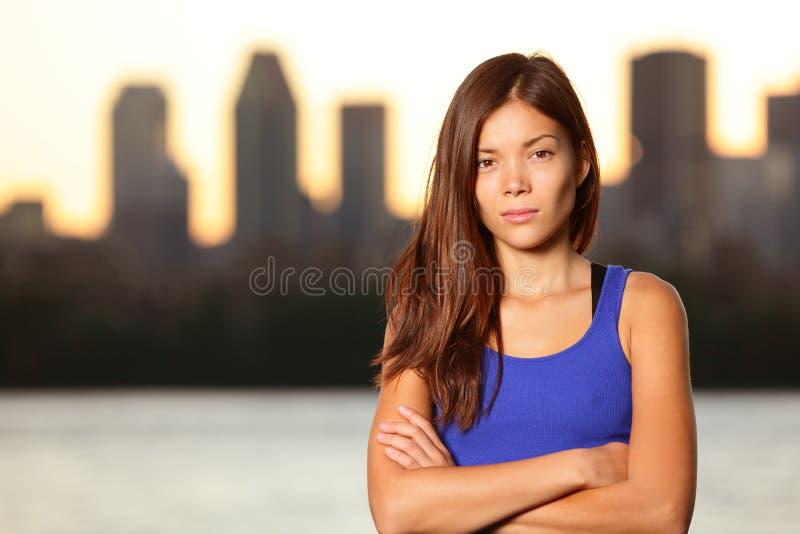 严肃的年轻都市女孩画象在城市 库存图片