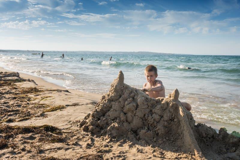 严肃看男孩大厦大沙子城堡 库存照片