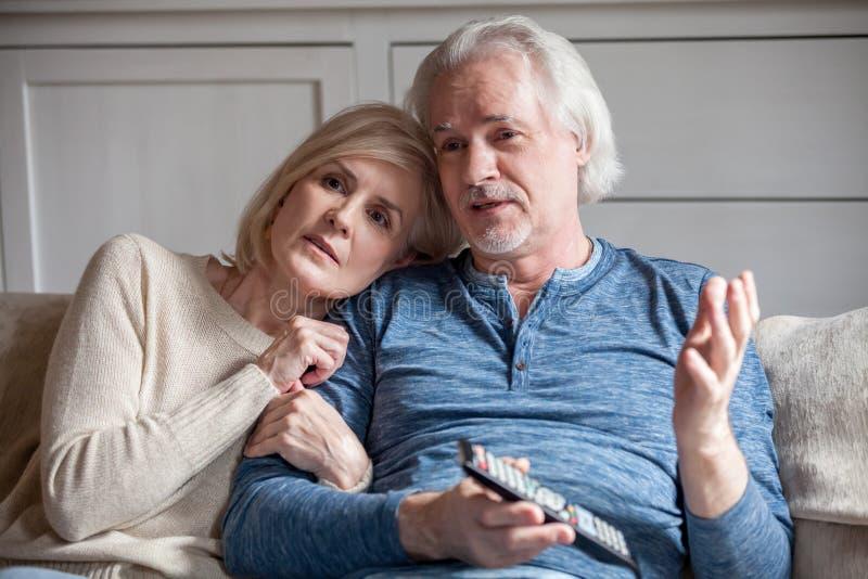 严肃资深夫妇拥抱谈的观看的电视一起在 免版税库存图片