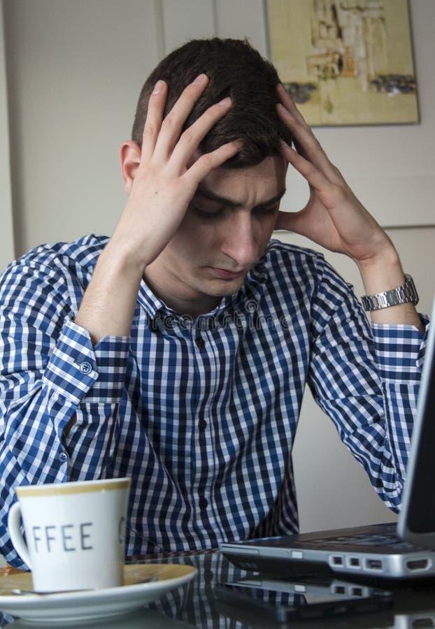 严肃年轻商人看在膝上型计算机屏幕办公室在家担心 免版税库存图片