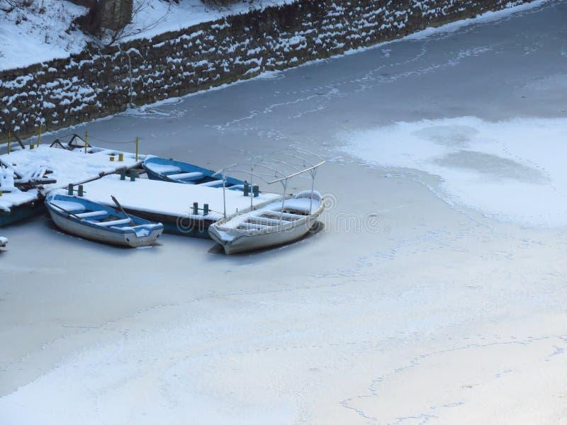 严重冬天 在水中结冰的三条小船 结冰的河,池塘,湖,海 免版税库存照片