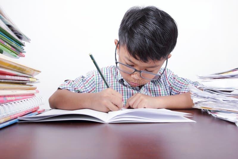 严重学习在书桌和白色背景上的亚裔男孩 免版税库存照片