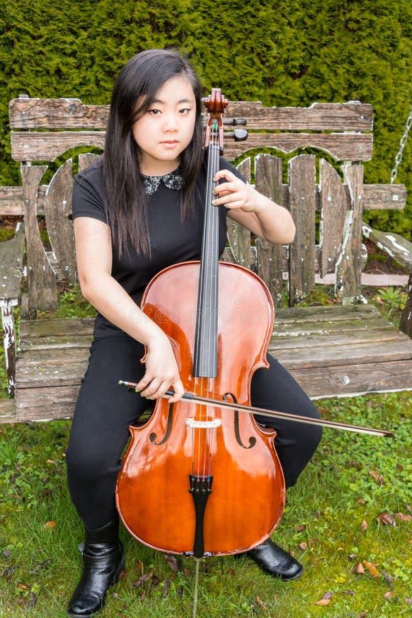 严重的青少年的使用的大提琴外面 库存图片