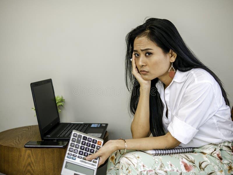 严重看对外面的咖啡店的美丽的亚裔女商人,内省考虑在工作的问题 免版税库存照片