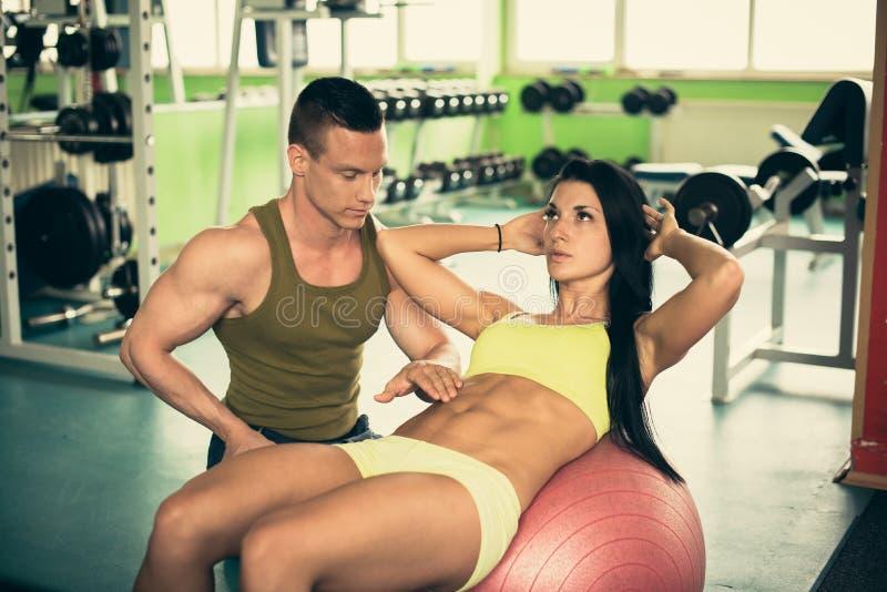 个人健身教练训练健身房的美丽的妇女 免版税库存照片