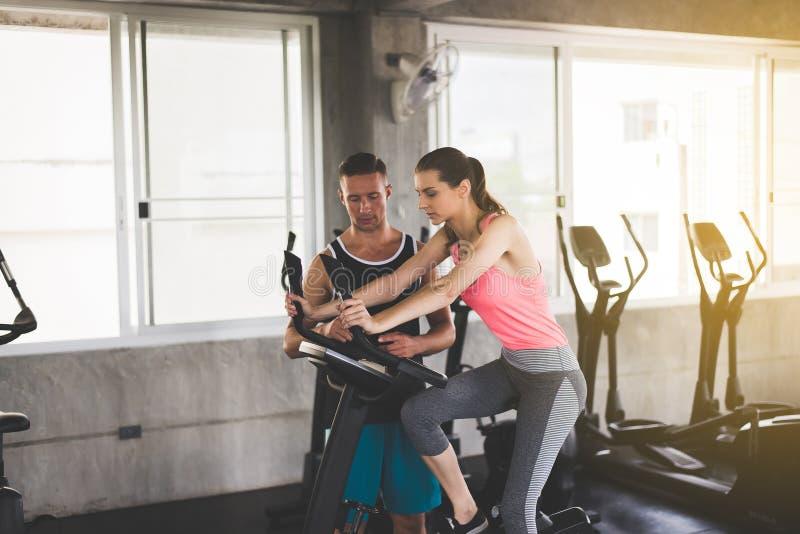 个人在健身房的教练员教练的妇女锻炼健康锻炼的概念和生活方式 图库摄影