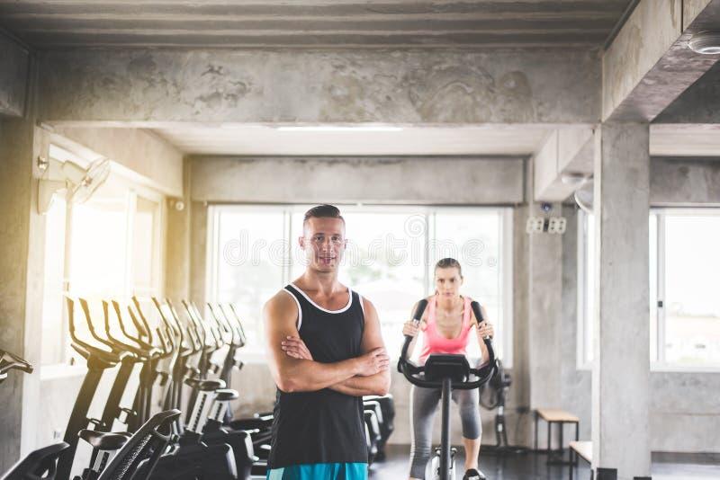 个人教练员人横渡了胳膊和教练妇女在健身房的锻炼健康锻炼的概念和生活方式 图库摄影