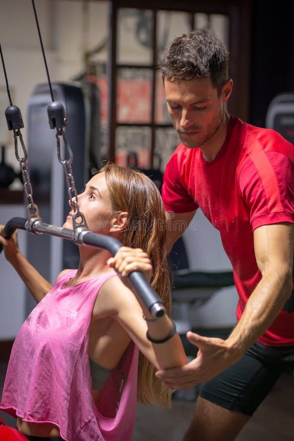 个人教练员协助训练的一个女孩 图库摄影