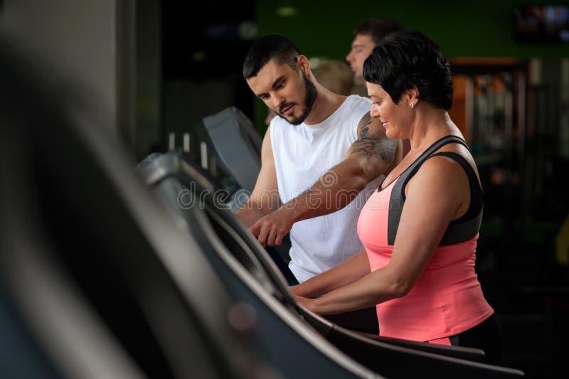个人教练谈话与健身房的女性客户 免版税库存照片