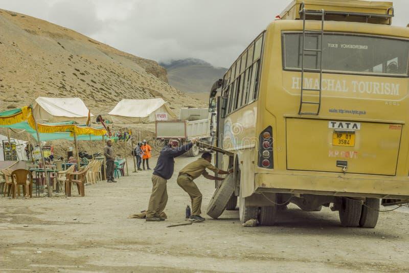 2个人更换被刺的轮子在公共汽车 免版税库存图片
