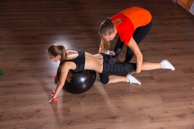 个人有锻炼球的教练员帮助的妇女 免版税库存照片