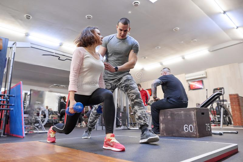 个人行使在健康俱乐部的健身辅导员帮助的夏天妇女 健康健身体育年龄概念 库存照片