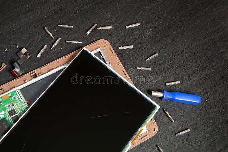 个人计算机片剂设备修理的过程在螺丝刀附近和咬住在黑木背景 拆卸 残破的玻璃,屏幕毁坏 免版税库存图片