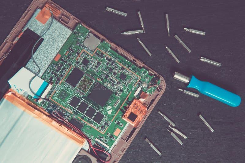 个人计算机片剂设备修理的过程在螺丝刀附近和咬住在黑木背景 顶视图 拆卸 库存照片