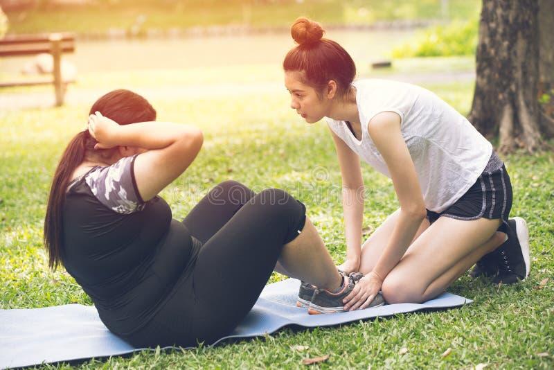个人训练饮食的教练员教练青少年的帮助肥胖女孩 免版税库存图片