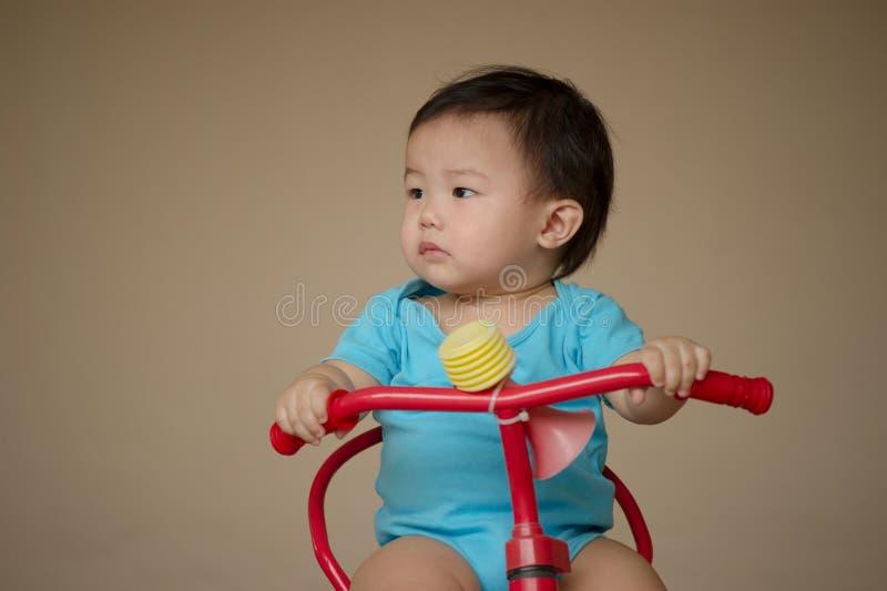 1个岁中国亚裔骑自行车的男孩佩带的连裤外衣 免版税库存图片