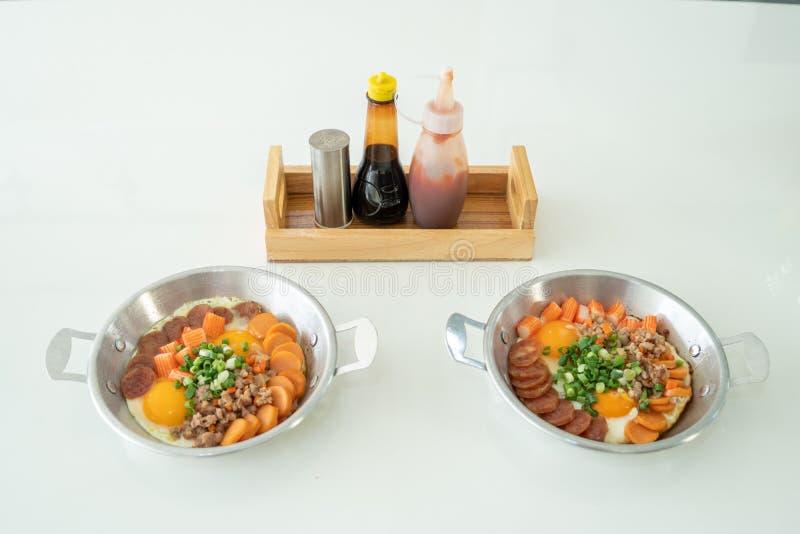 2个平底锅鸡蛋,安置在一张白色桌用调味品例如西红柿酱 库存照片