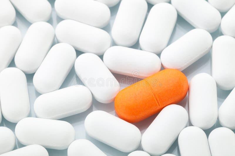 在白色之间的橙色药片一个 图库摄影